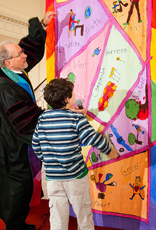 A quilt made by the RE kids illustrating the 7 UU Principles is shown to Rev. Robbins.